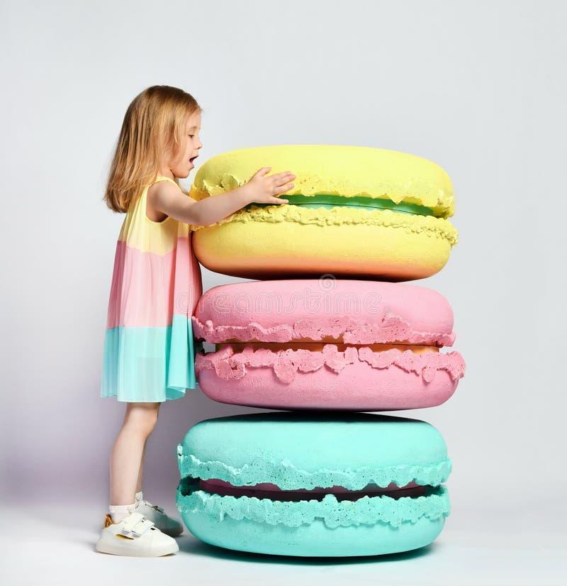 A menina bonito na roupa brilhante tem o divertimento nos macarons dos doces da decoração da sala do divertimento da festa de ano imagens de stock