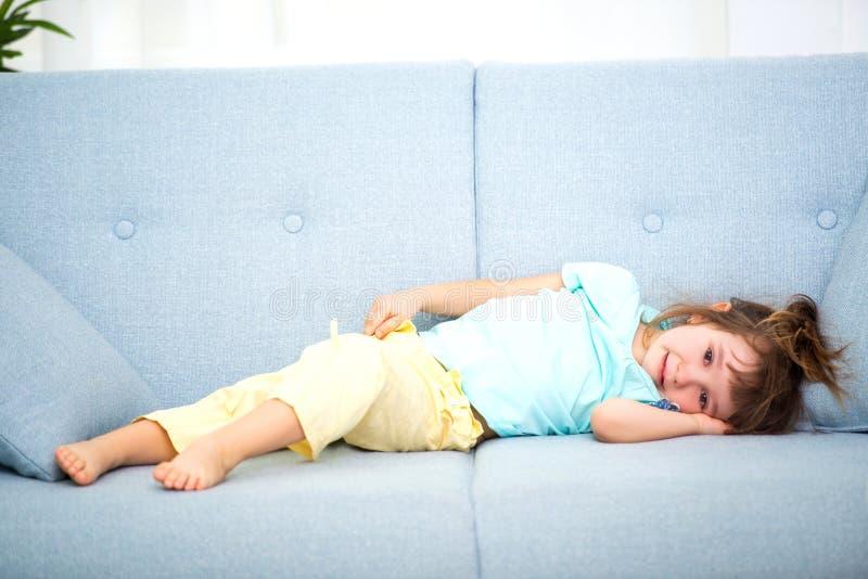 A menina bonito na roupa da casa encontra-se na sala no sofá imagem de stock