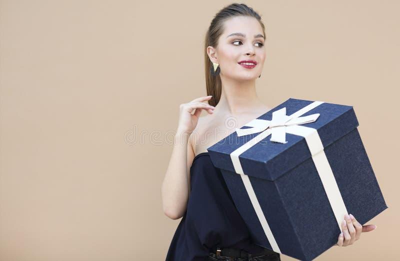 Menina bonito na roupa dos azuis marinhos que mant?m a caixa de presente grande isolada no bege fotos de stock