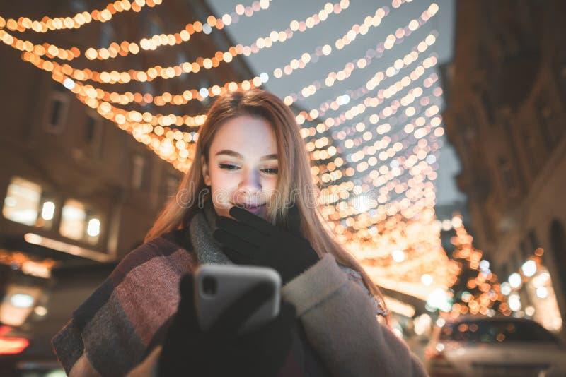 Menina bonito na roupa morna que está na noite na rua e que usa um smartphone no bokeh das luzes do fundo imagem de stock