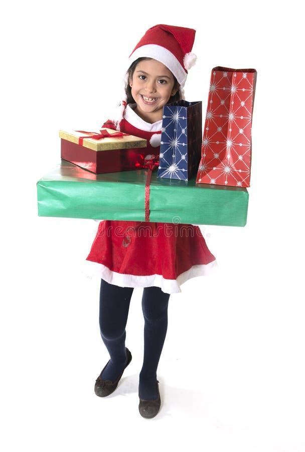 A menina bonito na terra arrendada feliz do traje de Santa Claus apresenta no Xmas foto de stock royalty free