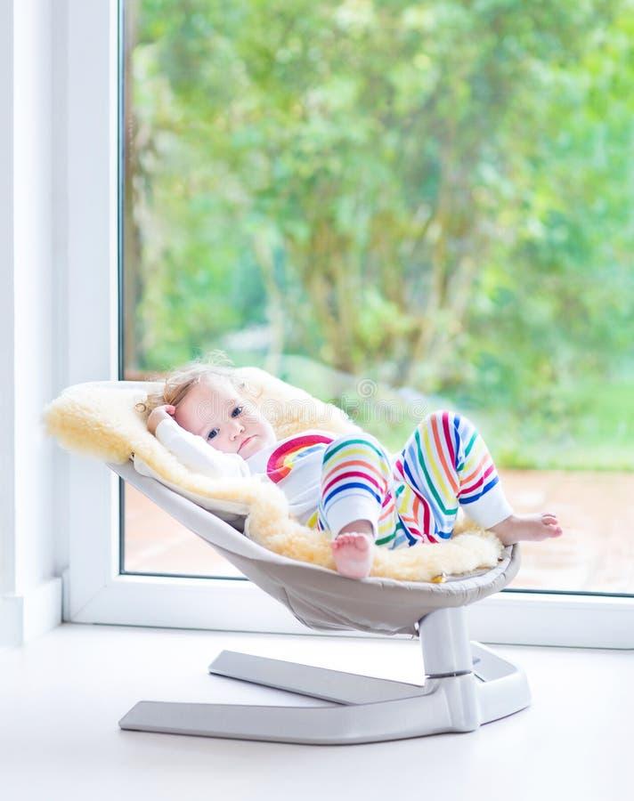 Menina bonito no balanço ao lado de uma janela grande fotos de stock royalty free