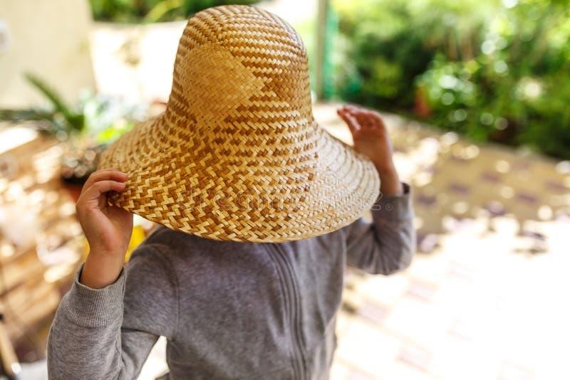 A menina bonito no chapéu de palha, salta exterior fotos de stock royalty free