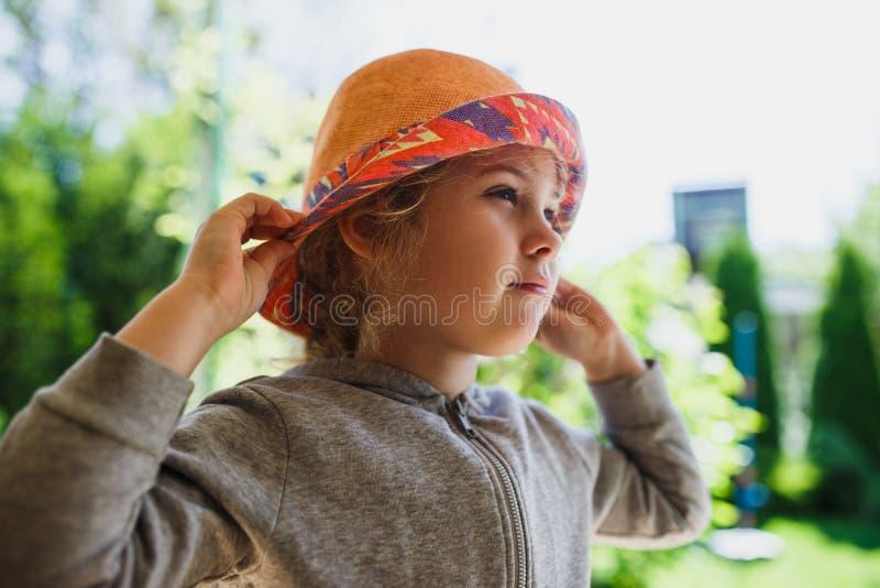 A menina bonito no chapéu de palha, salta exterior imagem de stock