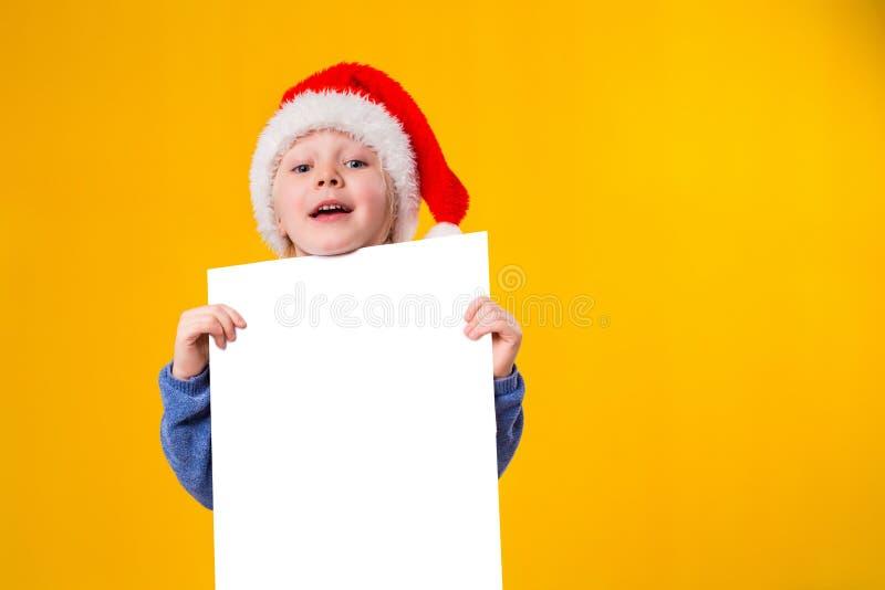 Menina bonito no chapéu de Santa Claus com uma folha branca do papel vazio Natal, x-mas, ano novo, inverno, pessoa fotografia de stock royalty free