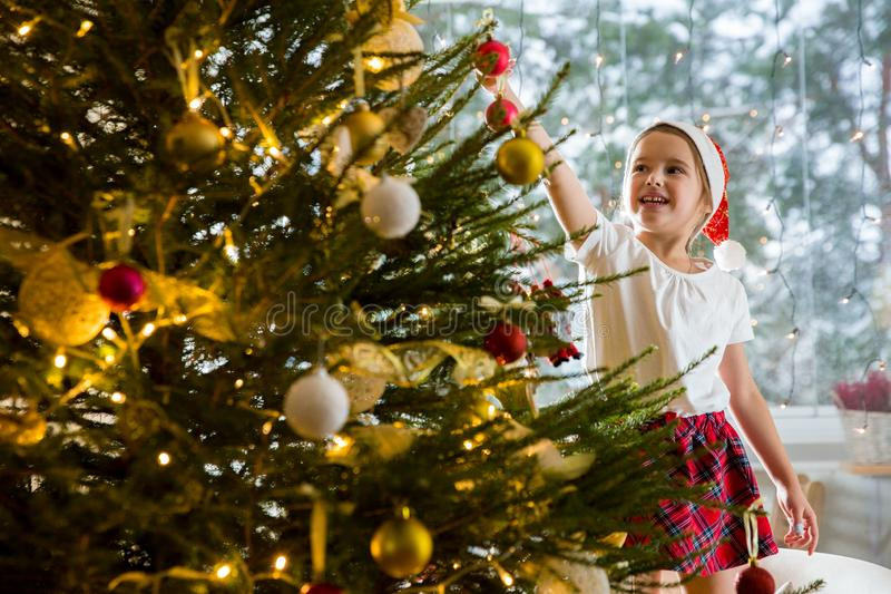 Menina bonito no chapéu de Santa e na saia de manta vermelhos que decora a árvore de Natal em casa fotografia de stock