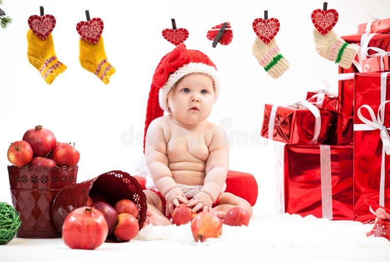 Menina bonito no chapéu de Santa que senta-se no assoalho imagem de stock