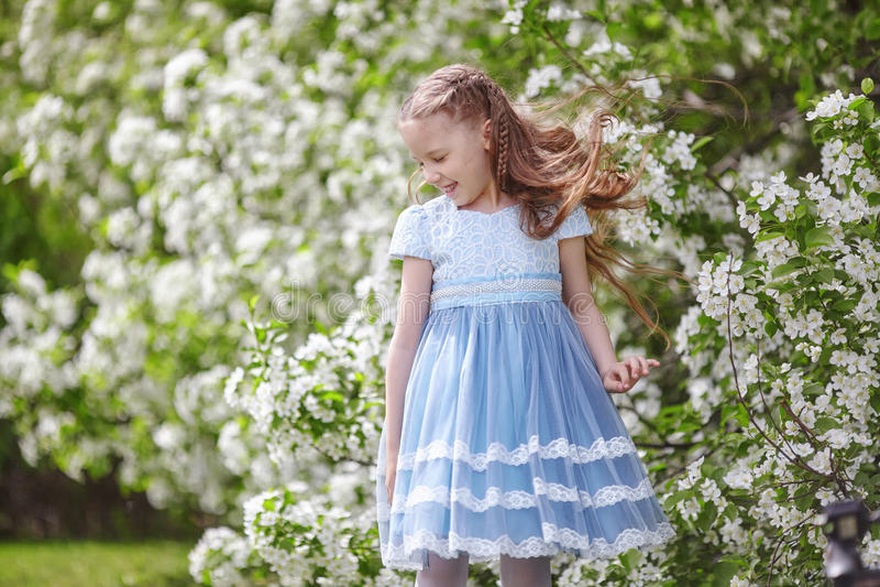 Menina bonito no jardim de florescência da árvore de maçã na mola imagens de stock royalty free