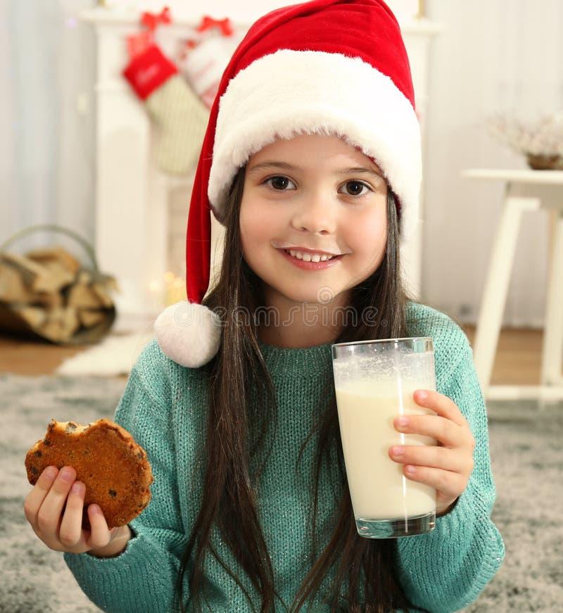 Menina bonito no leite bebendo e em comer do chapéu de Santa fotografia de stock royalty free