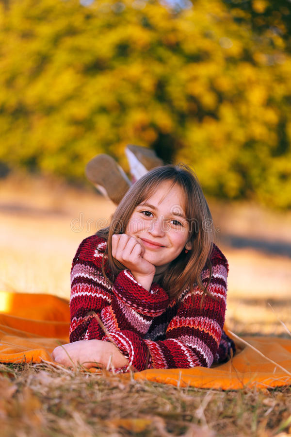 Menina bonito no outono, colocando ao ar livre imagem de stock