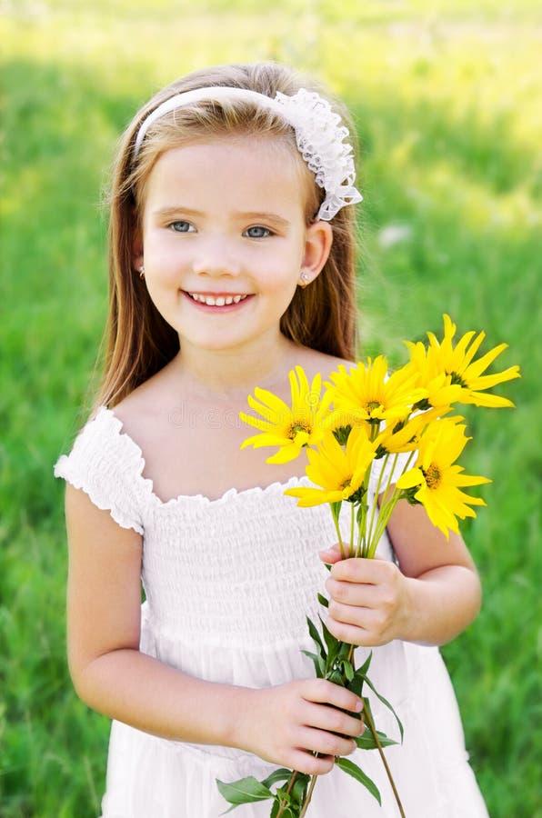 Menina bonito no prado com flores imagem de stock