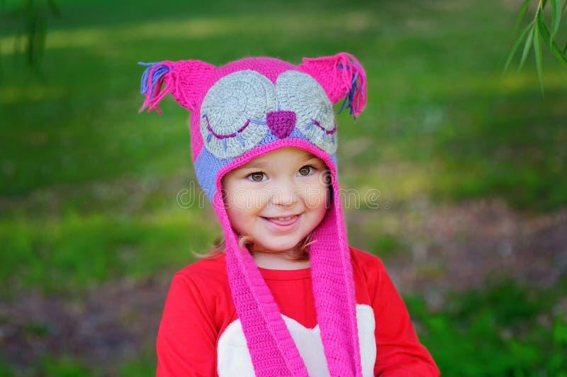 Menina bonito no prado no dia de verão uma coruja feita malha do chapéu foto de stock
