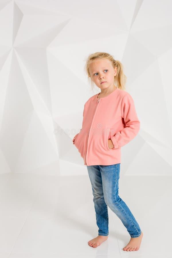 Menina bonito no revestimento e nas calças de brim cor-de-rosa, mãos em uns bolsos no fundo branco fotos de stock royalty free