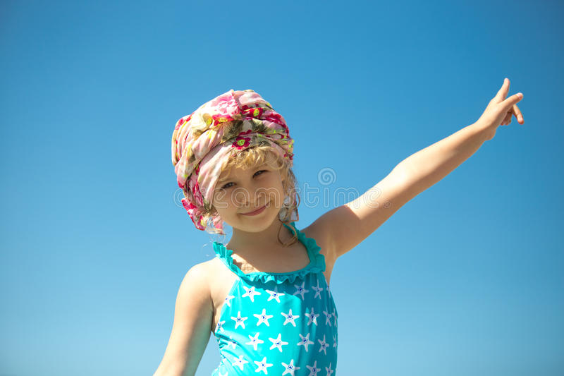 Menina bonito no roupa de banho contra o céu azul imagens de stock royalty free