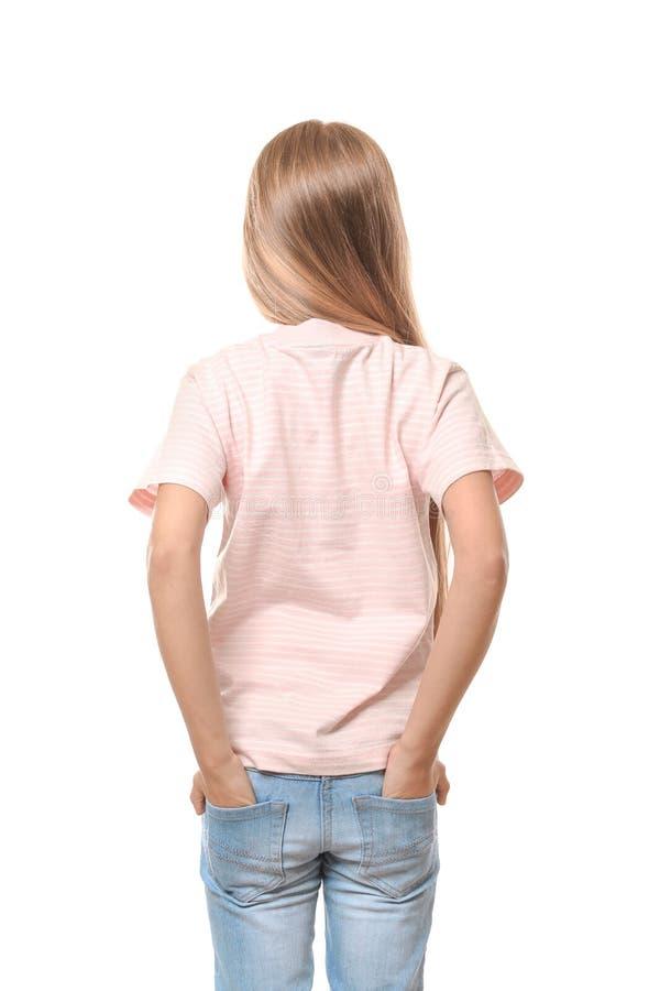 Menina bonito no t-shirt com mãos em uns bolsos no fundo branco, opinião da parte traseira imagens de stock