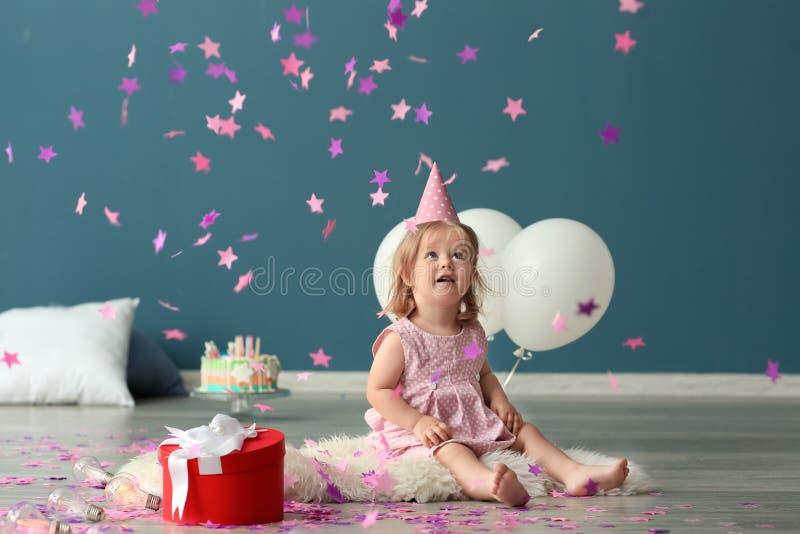 Menina bonito no tampão da festa de anos que joga com confetes do papel dentro foto de stock