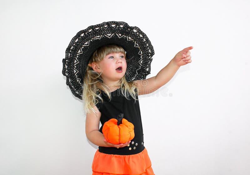 Menina bonito no traje da bruxa com abóboras Halloween Em um fundo branco imagens de stock