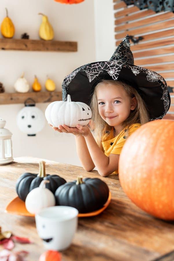 A menina bonito no traje da bruxa que senta-se atrás de uma tabela no tema de Dia das Bruxas decorou a sala, guardando a abóbora  imagens de stock