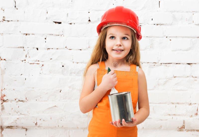 Menina bonito no uniforme alaranjado com lata da pintura nas mãos imagem de stock