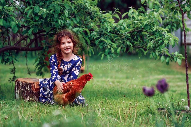 Menina bonito no vestido azul e na galinha vermelha imagem de stock