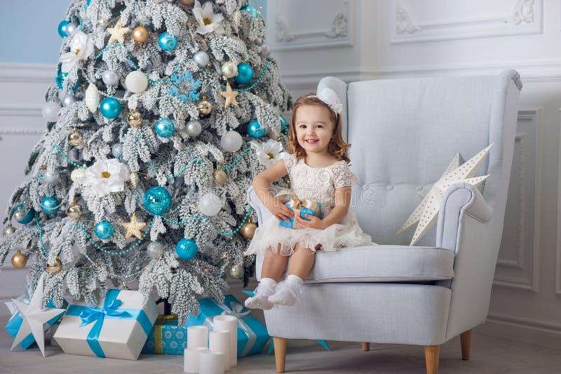 A menina bonito no vestido do bklom que senta-se em uma cadeira e abre a caixa com presente para o azul da árvore de Natal do fun foto de stock