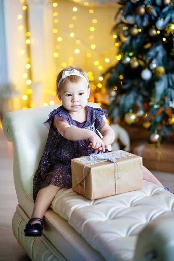 A menina bonito no vestido lilás que senta-se em uma cadeira e abre a caixa com presente para a árvore de Natal do fundo imagem de stock royalty free