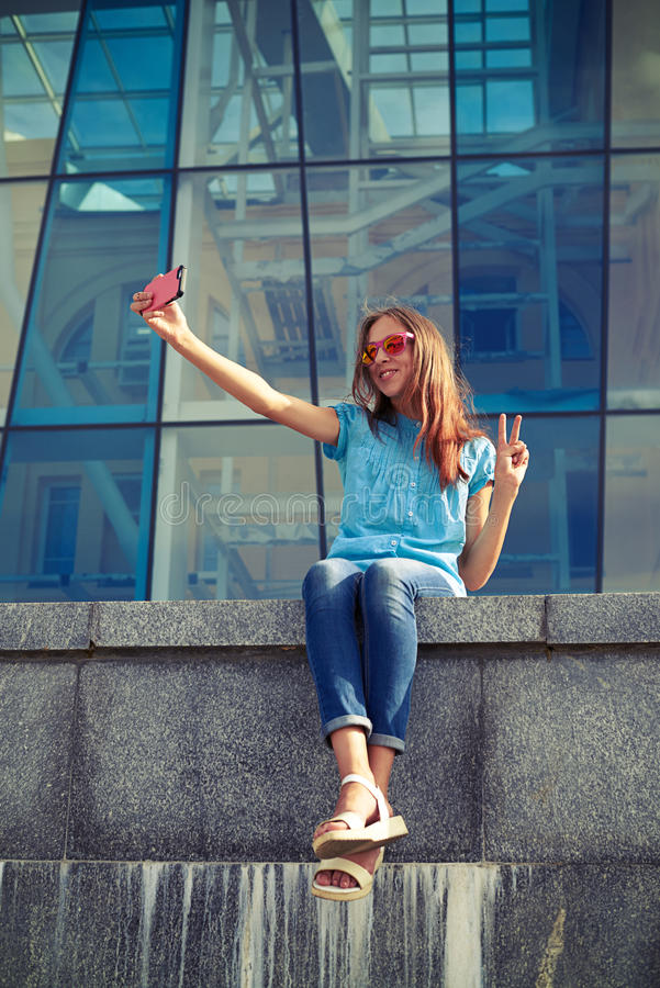 Menina bonito nos óculos de sol à moda que tomam o selfie ao sentar-se dentro fotografia de stock royalty free