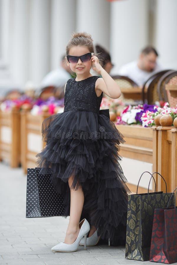 A menina bonito nos óculos de sol e em um vestido de nivelamento bonito vai comprar em um boutique prestigioso imagem de stock