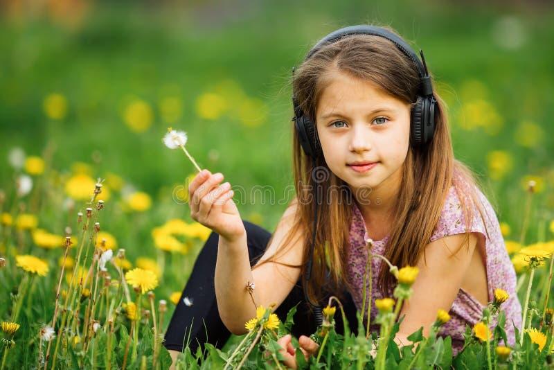 Menina bonito nos fones de ouvido que aprecia a música na natureza foto de stock