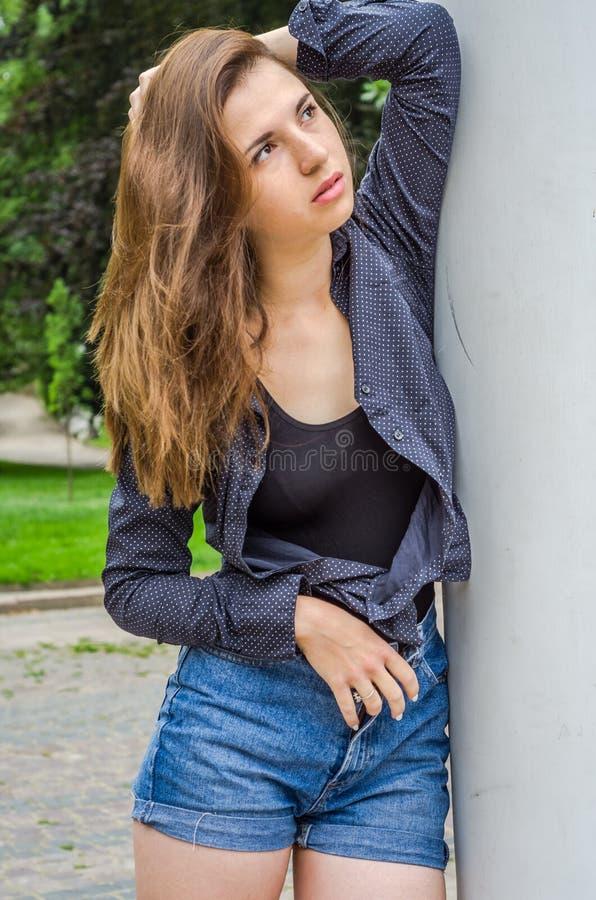 Menina bonito nova com cabelo longo no short de uma camisa e da sarja de Nimes que anda no parque no dia de verão ensolarado de L fotos de stock
