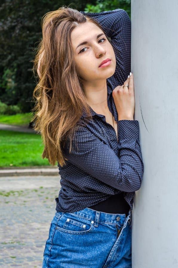 Menina bonito nova com cabelo longo no short de uma camisa e da sarja de Nimes que anda no parque no dia de verão ensolarado de L imagens de stock