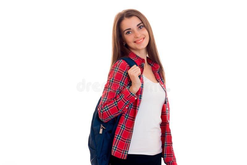 Menina bonito nova em uma camisa de manta e com uma pasta nos olhares traseiros na câmera e no sorriso fotos de stock
