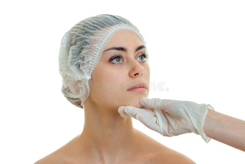 A menina bonito nova no chapéu médico do cabelo veio ao esteticista e olha sua cara na luva branca foto de stock