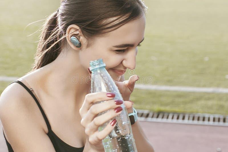 A menina bonito nova no sportswear bebe a água de uma garrafa plástica Retrato emocional fotos de stock