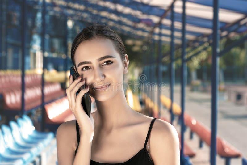 A menina bonito nova no sportswear está chamando o smartphone fotografia de stock