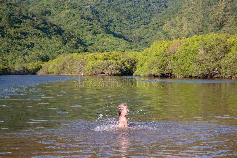 Menina bonito nova que joga na água em um rio bonito em um dia de verão ensolarado foto de stock royalty free