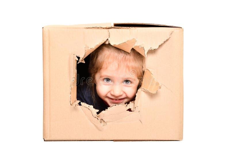 A menina bonito olha fora de um furo rasgado em uma caixa imagens de stock