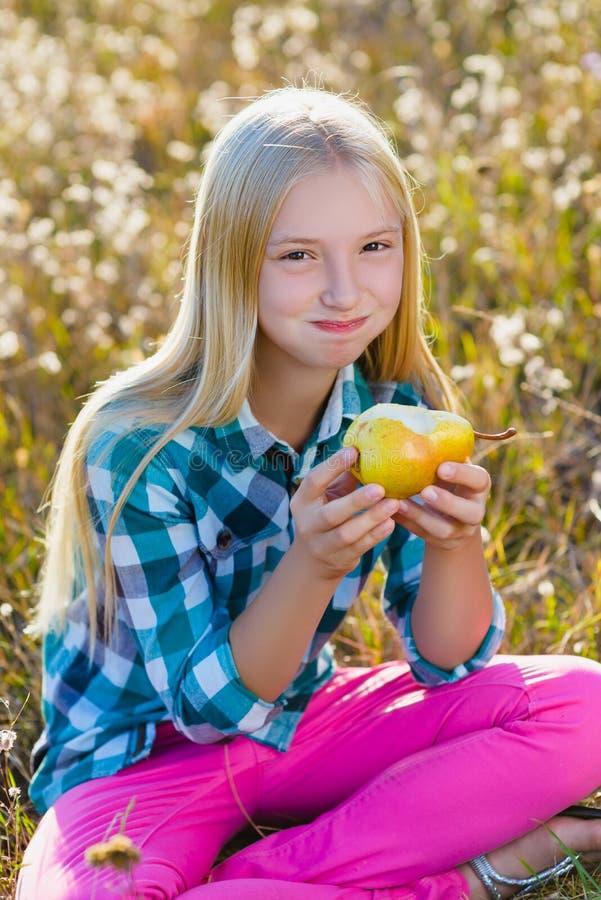 Menina bonito ou pera saudável e suculenta comida adolescente exterior imagens de stock royalty free
