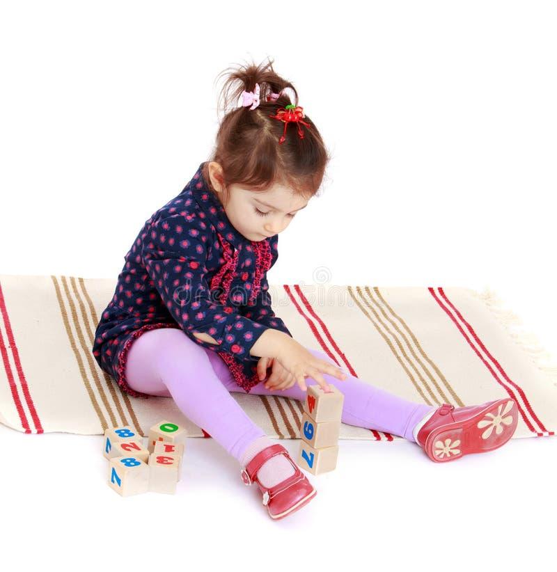 A menina bonito põe os cubos que sentam-se no tapete imagem de stock royalty free