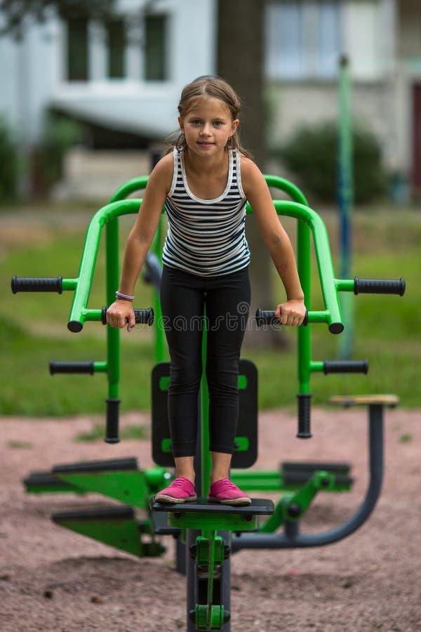 A menina bonito pequena é contratada no material desportivo exterior esporte fotos de stock