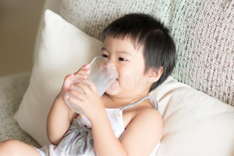 A menina bonito pequena asiática é guardando e bebendo um vidro do leite mim foto de stock