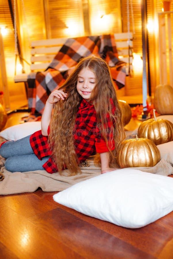 Menina bonito pequena com cabelo encaracolado longo perto do balanço e abóboras em um vermelho em uma camisa quadriculado vermelh imagem de stock royalty free