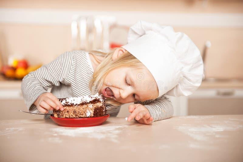 Menina bonito pequena com chapéu do cozinheiro chefe que come o bolo fotos de stock royalty free