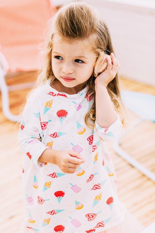 Menina bonito pequena com a concha do mar nas mãos na praia tropical imagem de stock royalty free