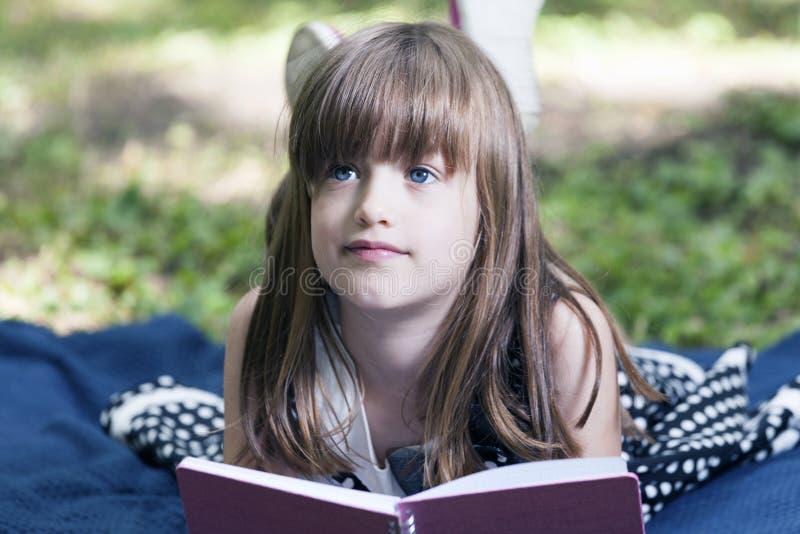 A menina bonito pequena com olhos azuis bonitos encontra-se sobre e aprecia-se o natu foto de stock royalty free