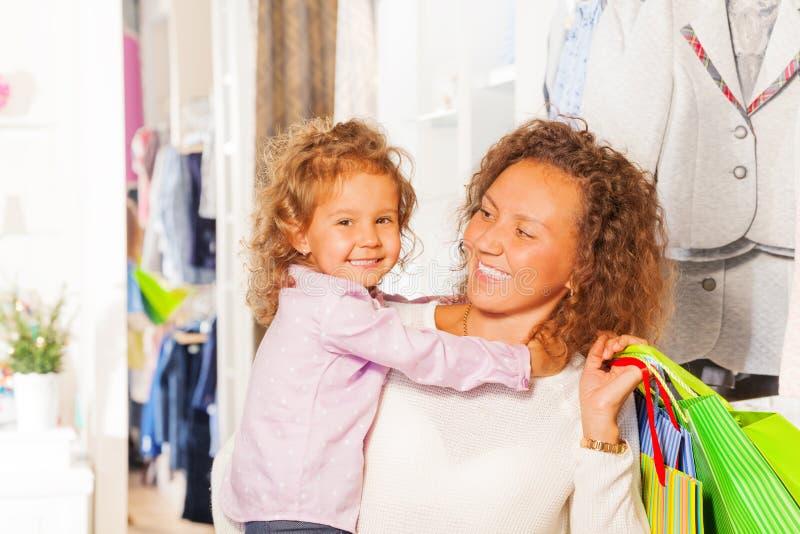 Menina bonito pequena com sua compra bonita da mãe fotos de stock