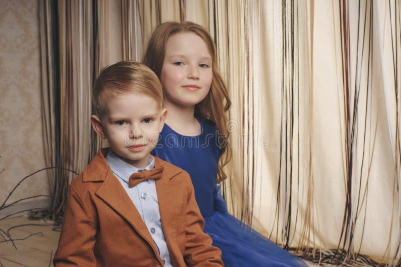 Menina bonito pequena do menino que abraça o jogo no fundo branco, o fim feliz da família acima do irmão e o sorriso da irmã fotos de stock royalty free