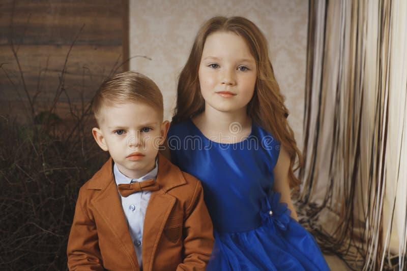 Menina bonito pequena do menino que abraça o jogo no fundo branco, fim feliz da família isolado acima Sorriso do irmão e da irmã imagens de stock royalty free