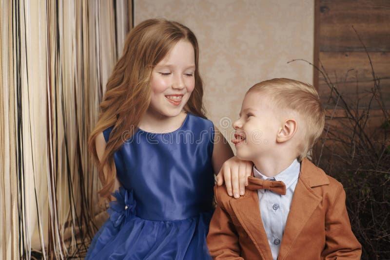 Menina bonito pequena do menino que abraça o jogo no fundo branco, fim feliz da família isolado acima Sorriso do irmão e da irmã foto de stock