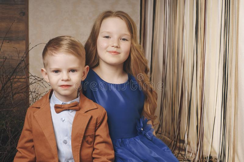 Menina bonito pequena do menino que abraça o jogo no fundo branco, fim feliz da família isolado acima Sorriso do irmão e da irmã imagem de stock